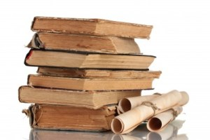 a stack of old books and a scroll