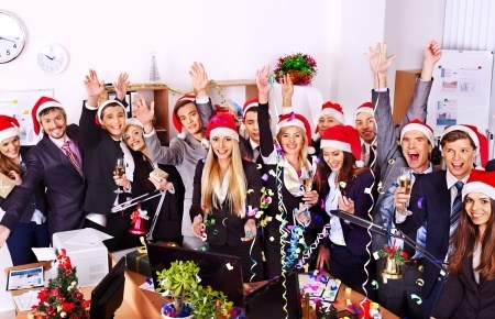 a Christmas party with a group of people waving at the camera