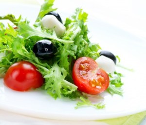 a plate of salad with an olive and a cut tomato