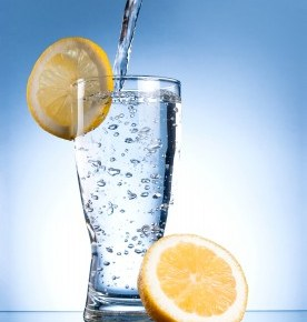 a glass of water with a lemon on the glass.