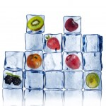 ice cubes stacked with frozen fruit in some of the cubes