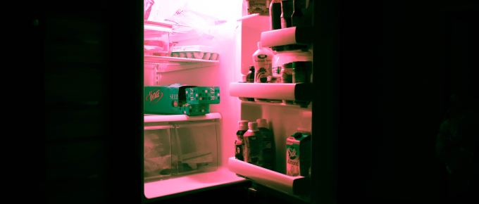 a refrigerator with an open door and pink light coming out