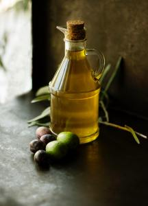 a beautiful bottle of fresh olive oil with big green olives aritting around it on a wooden table