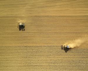 2an ariel view of 2 tractors in dry farm field