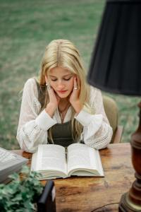 a beautiful blond girl reading a book