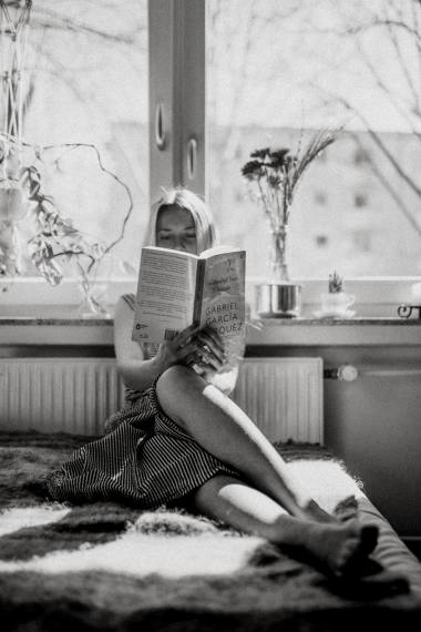 a girl reading a book sitting on her sofa