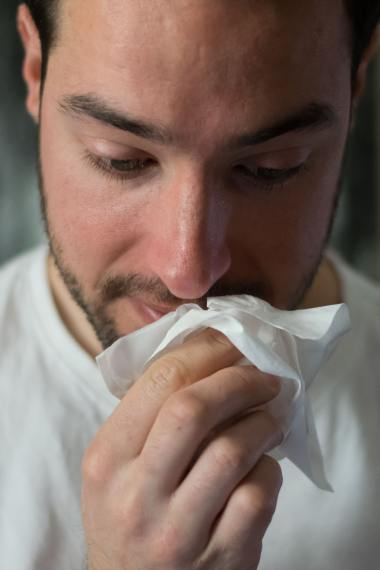 a young man wiping his nose