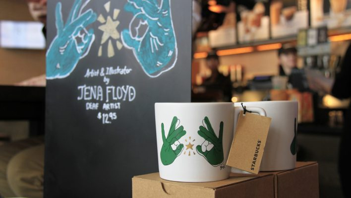 "A mug showing two hands signing the word ""Starbucks"", and a sparkling gold star between the hands. Art illustrated by Jena Floyd, a local deaf artist."