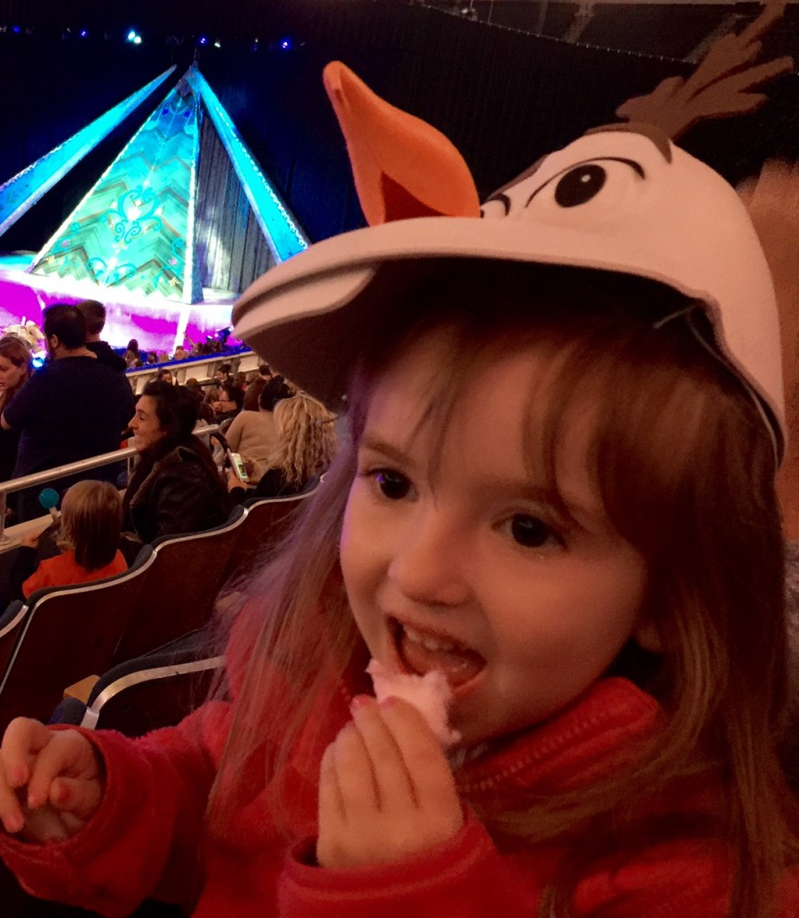 Lily Eating Cotton Candy in Her Olaf Hat
