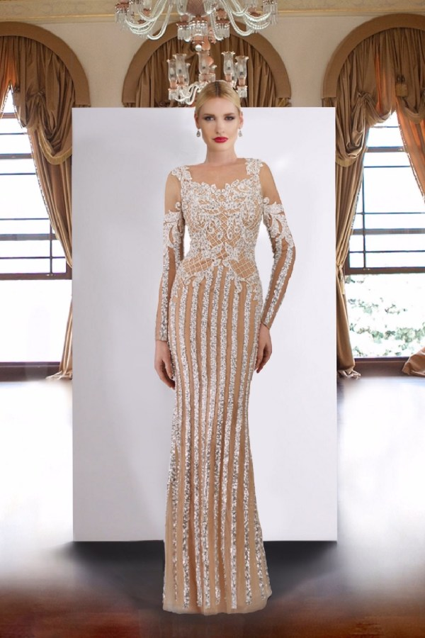 Embroidered applique sheer long sleeve gown in ivory nude. Beaded long dress with sleeve by Janique. Designer sequin gown.