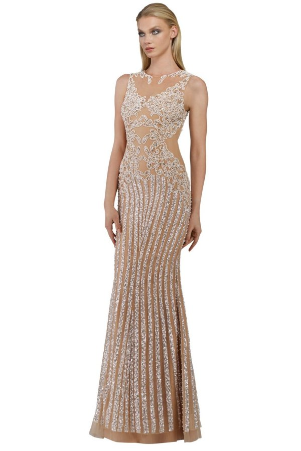 Long beaded applique gown in ivory with no sleeves. Embroidered sleeveless sequin dress by Janique in ivory.
