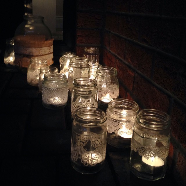 candles in glass jars, decorated with lace, on the doorstep for my daughter's birthday party