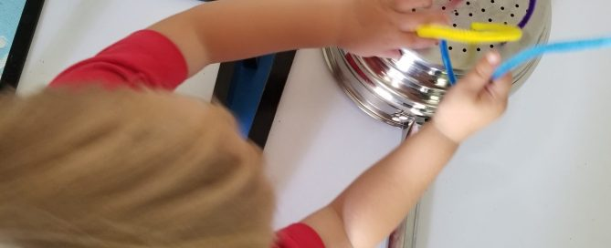 boy playing with pipe cleaners in a colander - 5 Simple Toddler Activities