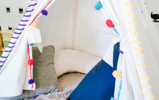 Personalize your playroom teepee with a fun DIY design and pom poms.