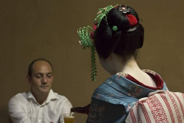 En maiko (ung geisha) häller upp öl åt reseledaren Dennis