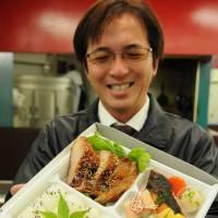 Etsushi Ohashi shows a bento boxed meal his company will start selling at the Okazaki service area. | CHUNICHI SHIMBUN