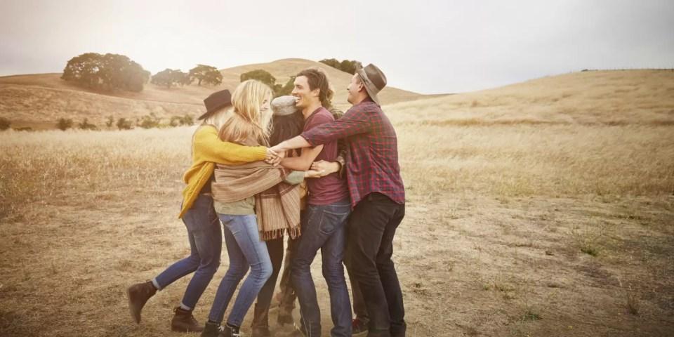 Friends hugging in rural landscape
