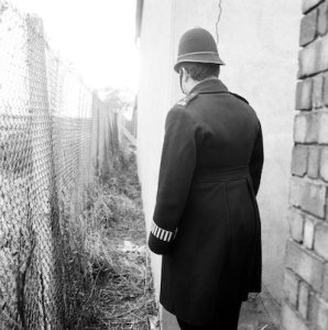 Criime Scene in Acton where the body of Bridget O'Hara was found earlier today 16th February 1965.  Pictured: Policeman standing at spot where body was found, in between fence (on left) and brick hut near embankment.  Bridget O'Hara was a confirmed victim of serial killer known as 'Jack the Stripper' who was operating in London 1964-1965 and killed 6-8 women prostitutes & dumped their bodies around london or in the River Thames.  The serial killer has never been caught.