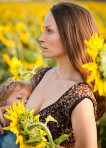 young woman breastfeeding baby in spring sunflower field