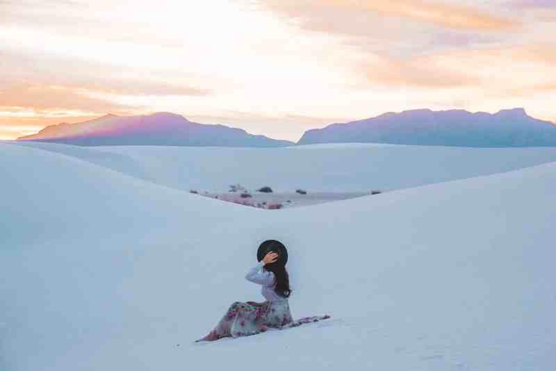 girl sitting on sand at white sands national monument