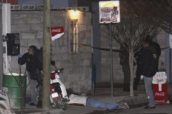 Peritos forenses investigan en busca de pruebas junto a la vivienda donde se perpetró la matanza. (Agencia EFE)