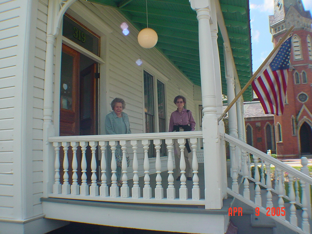 Two women pose for a photo in 2005 on the porch of a house built in 1879.