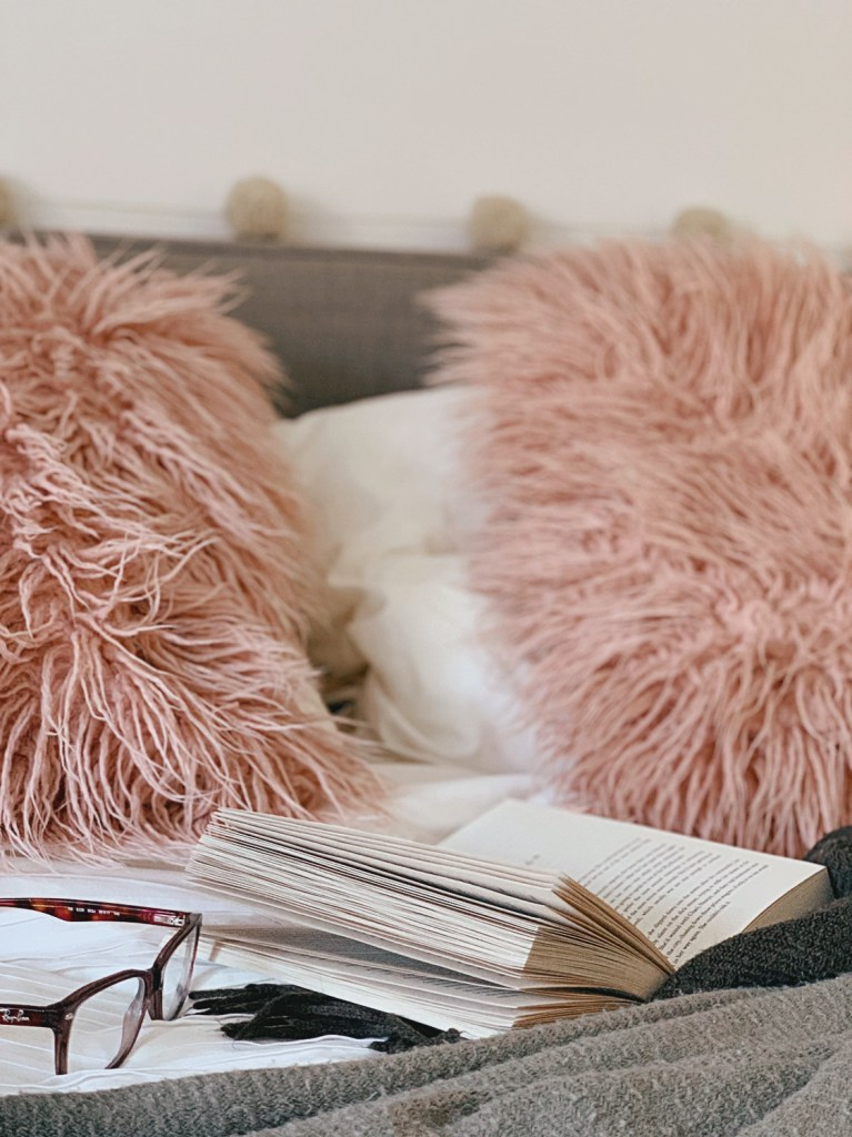 White bedding, grey blanket, open book and glasses, pink fluffy cushions