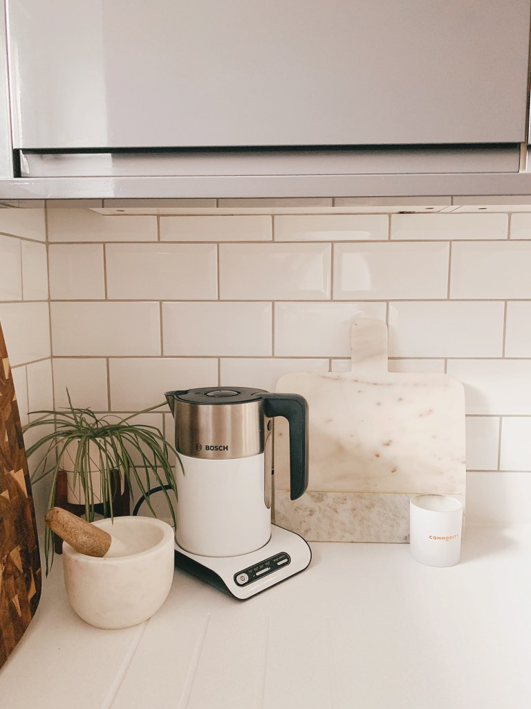 kitchen white worktop subway tile kettle marble chopping board spider plant