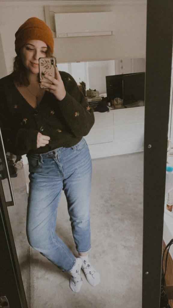 Jaye rockett taking a selfie in the mirror of her bedroom. She is wearing light wash boyfriend fit jeans, a green cardigan and an orange hat.