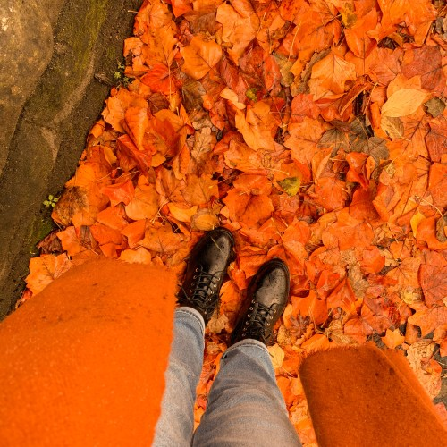 Shot taken from above looking down at Jaye's feet. She is wearing black combat boots and light wash jeans, and stood on a pile of crisp autumn leaves.