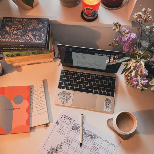 A desk viewed from above with a laptop, scattered papers and notebooks, coffee, flowers and fairytale books