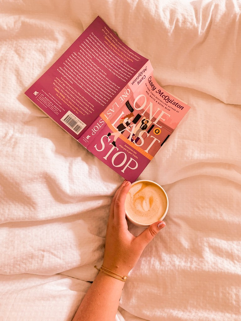 One last stop by casey mcquiston is open on a bed with white sheets, and my arm holds a coffee with swirly foam.