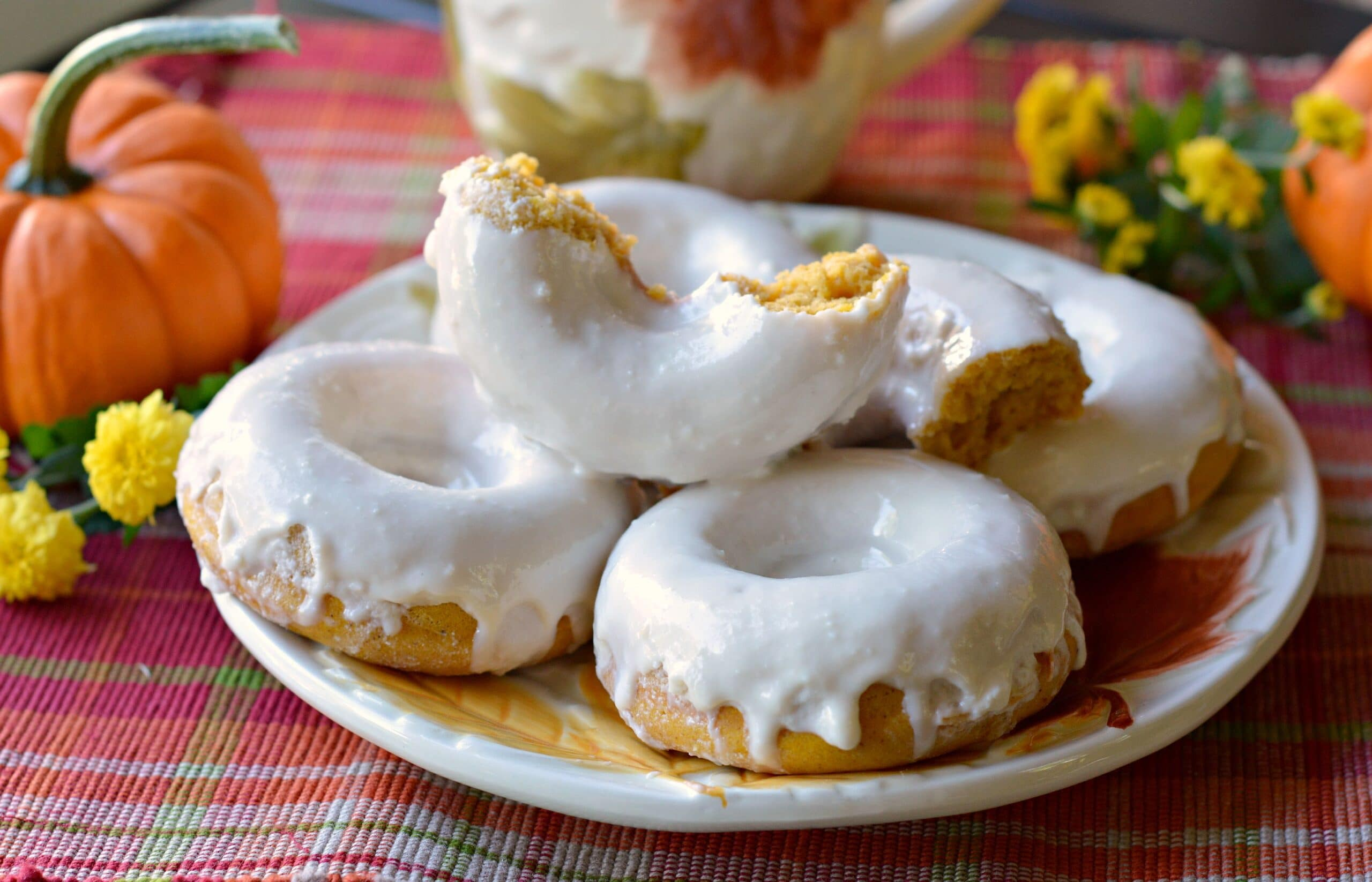 Baked Buttermilk Pumpkin Donuts Stacked On Plate. Calling all pumpkin lovers! Try my moist Baked Buttermilk Pumpkin Donut Recipe. Frosted with cream cheese and baked to perfection in my No Yeast Recipe.