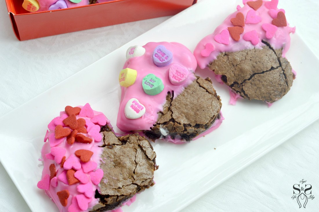 Valentine's Day Fudgy Brownies on plate. A from-scratch Valentine's Day Fudgy Brownie recipe, stuffed with butterscotch chips. Dipped in chocolate and then topped with candy hearts and sprinkles.