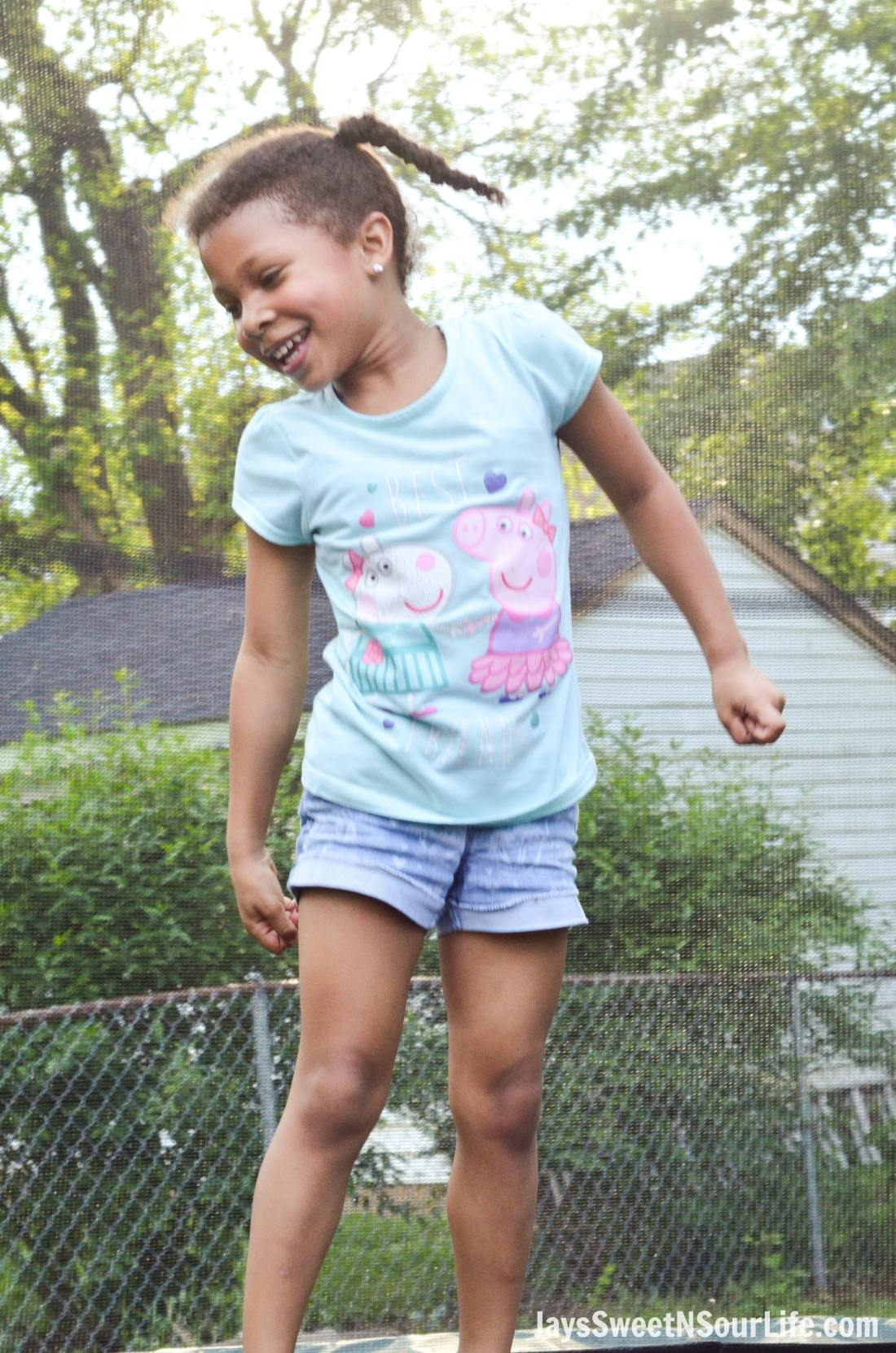 Little african american girl smiling and jumping on a trampoline. Attending a Beach Sundae Party.