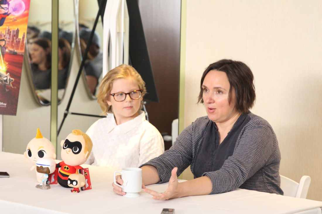 Incredibles 2 Interview with Sarah Vowell & Huck Milner sitting at table. Voice actors of Dash and Violet Parr Tell All in this revealing exclusive interview.