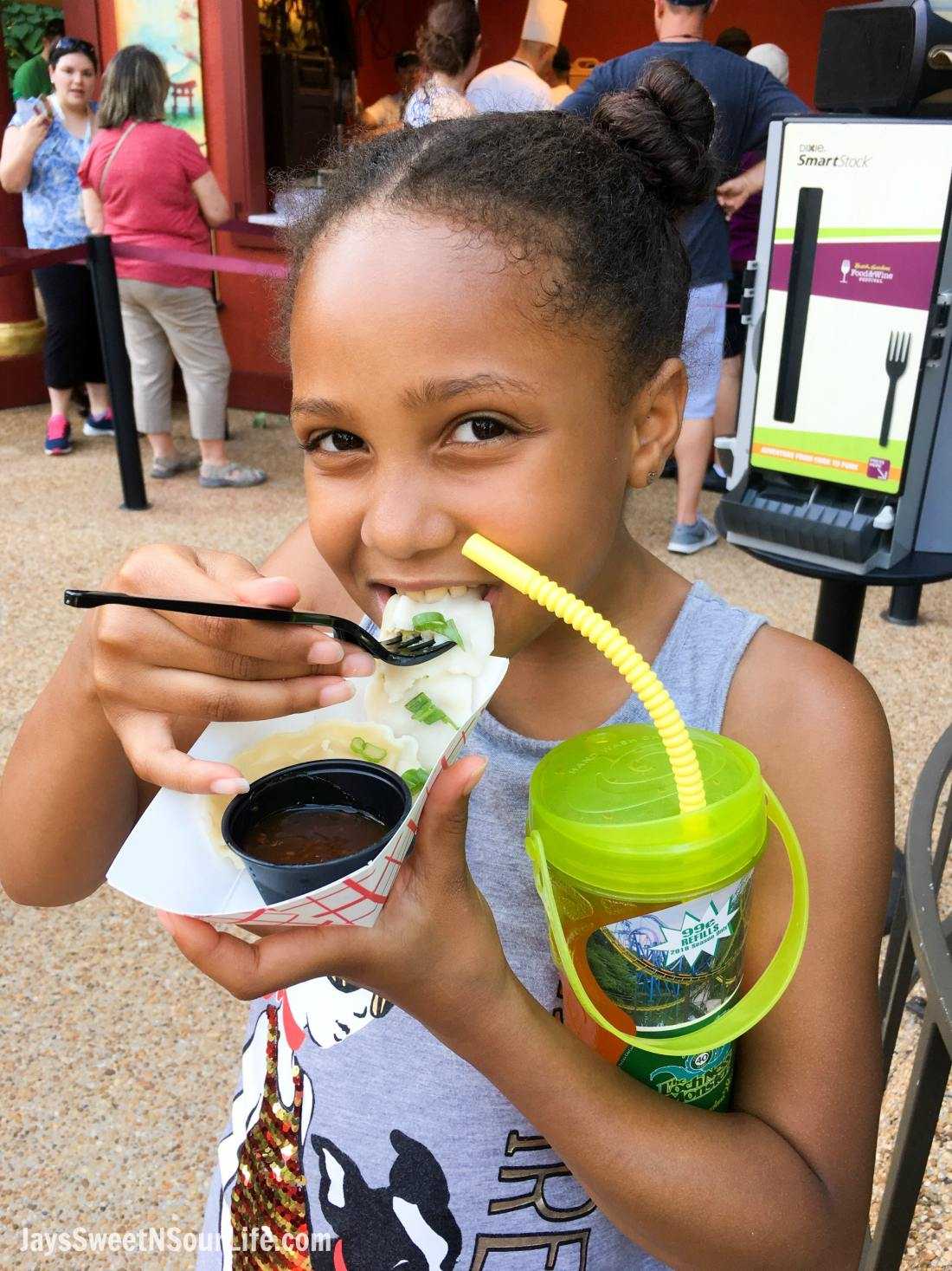Girl eating dumpling Japan 2018 Busch Gardens Food and Wine Festival. Food & Wine Festival is from 11 am to close every Friday, Saturday and Sunday, May 25 - July 1.