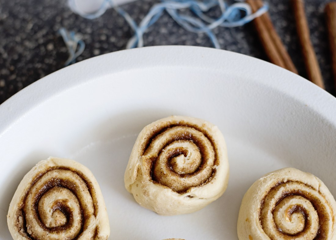 Pumpkin Spice Cinnamon Rolls Closeup In Pan. Fill your home with the delicious smell of these easy to make Pumpkin Spice Cinnamon Rolls.