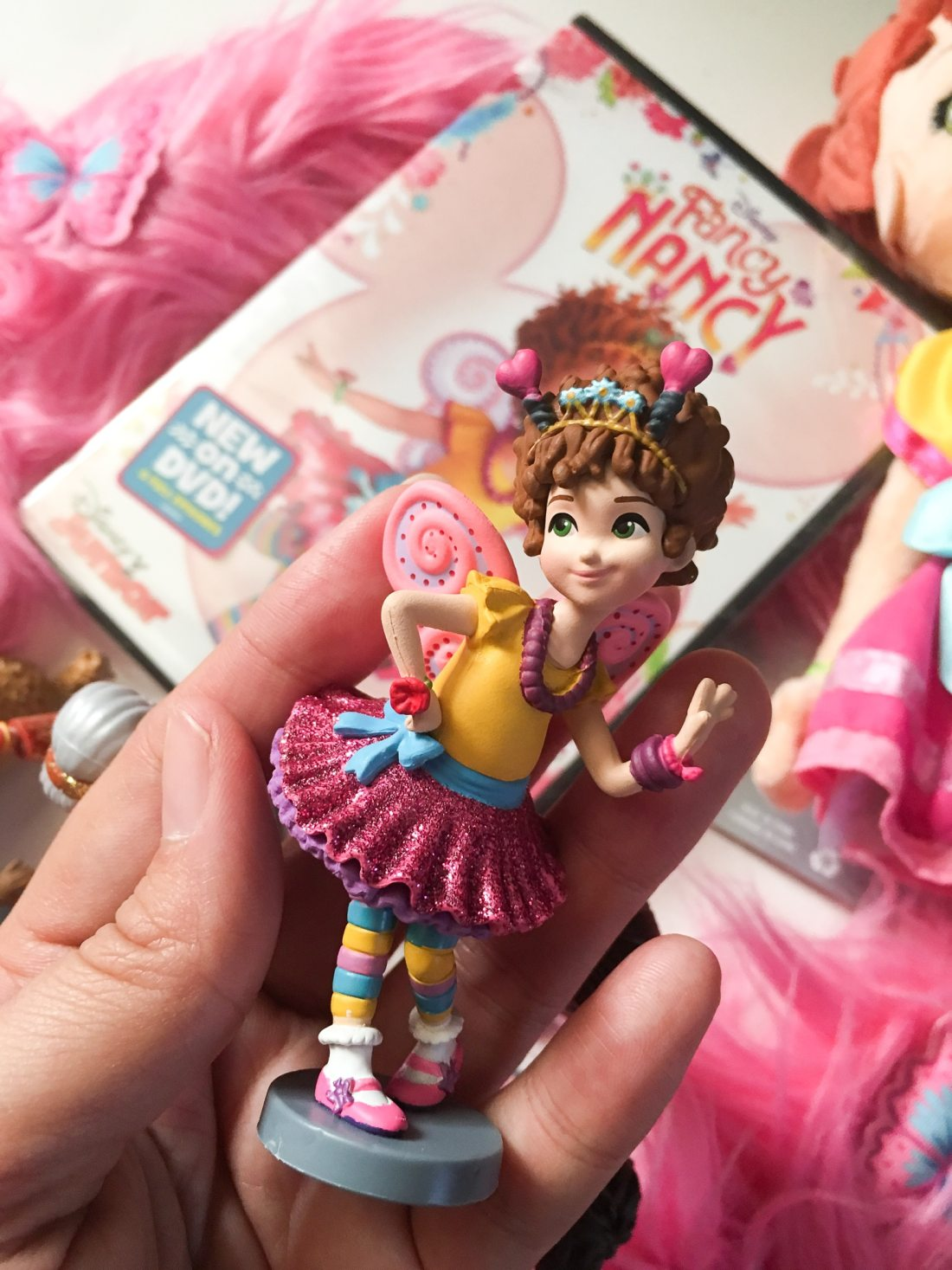 """Fancy Nancy Figure Nancy. Grab some glitter, add a dash of """"ooh la la,"""" sprinkle in original songs and Voilà! Get set to pour on the fun with Fancy Nancy in her newest DVD from Disney Junior."""