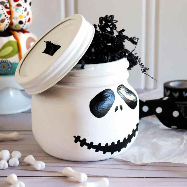 Jack Skellington Mason Jar Side View. This Jack Skellington Mason Jar Halloween Craft is the perfect way to creep your way into the Halloween season. Fill it with your favorite candies and treats, it's the perfect Halloween Craft that you can keep or gift.