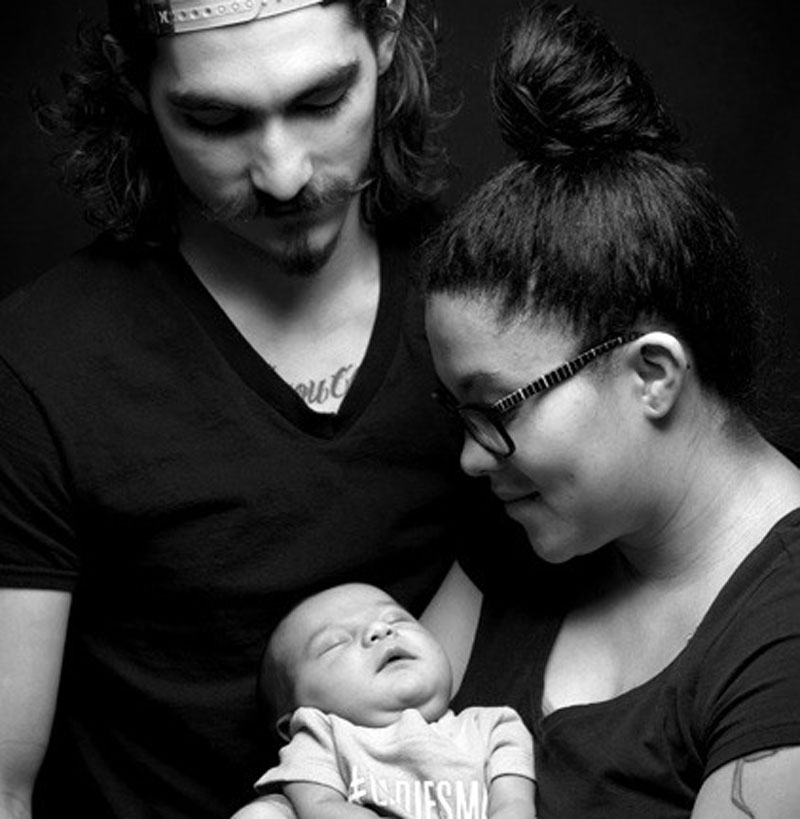 First time mother and father admiring their newborn baby in black and white