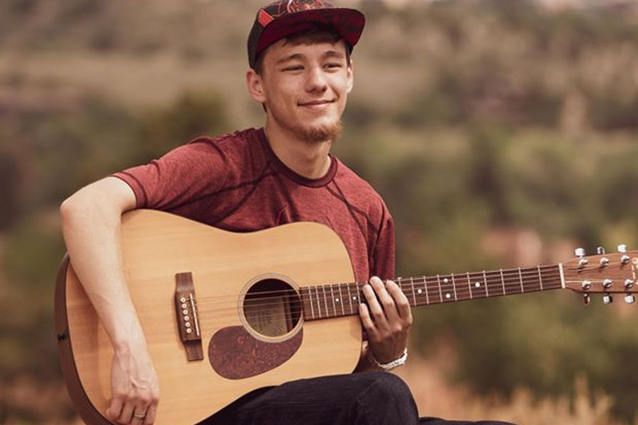 Young man posing with his guitar in an open field in Colorado Springs, CO