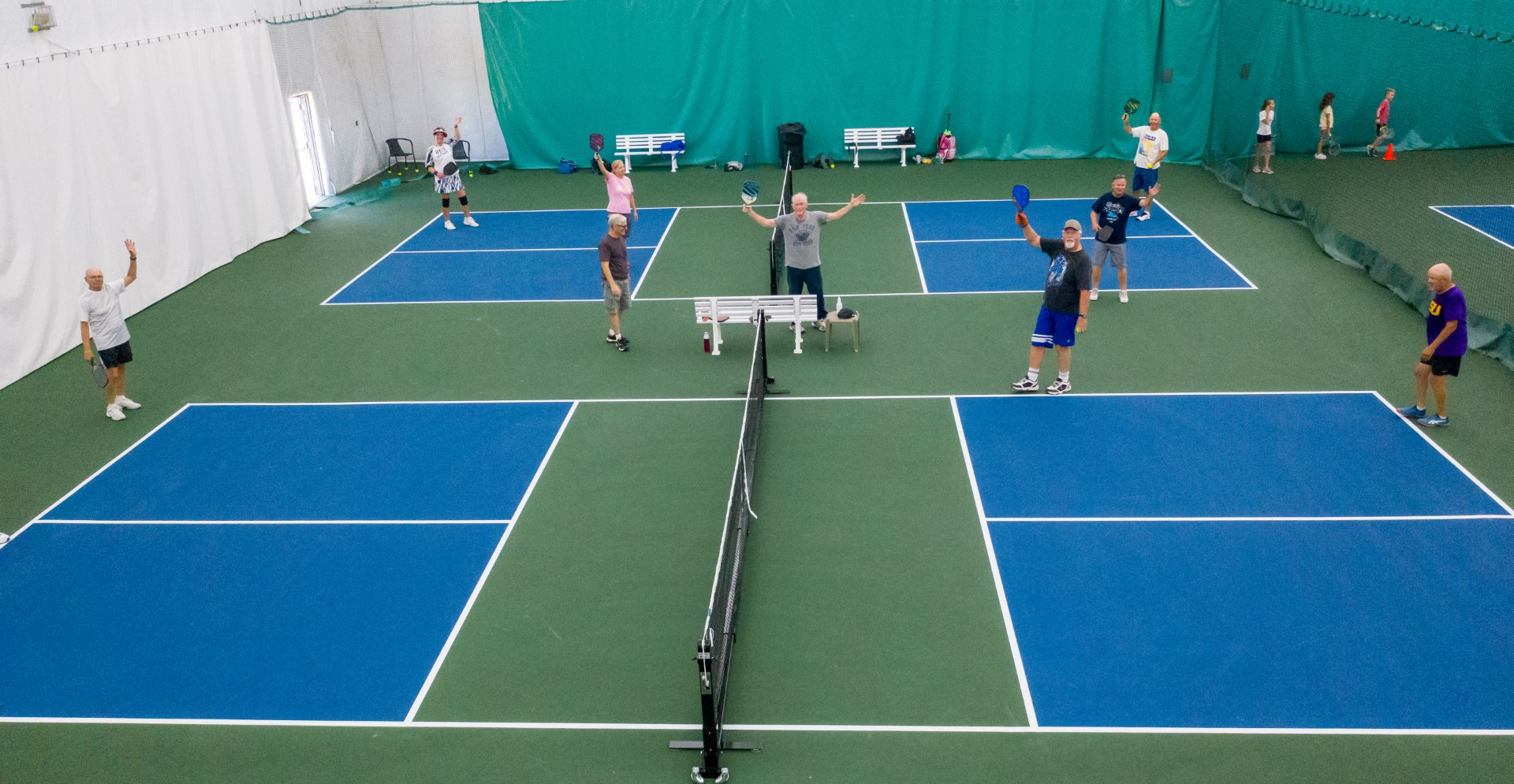 Indoor aerial view of senior citizens playing pickle on blue courts inside a club house