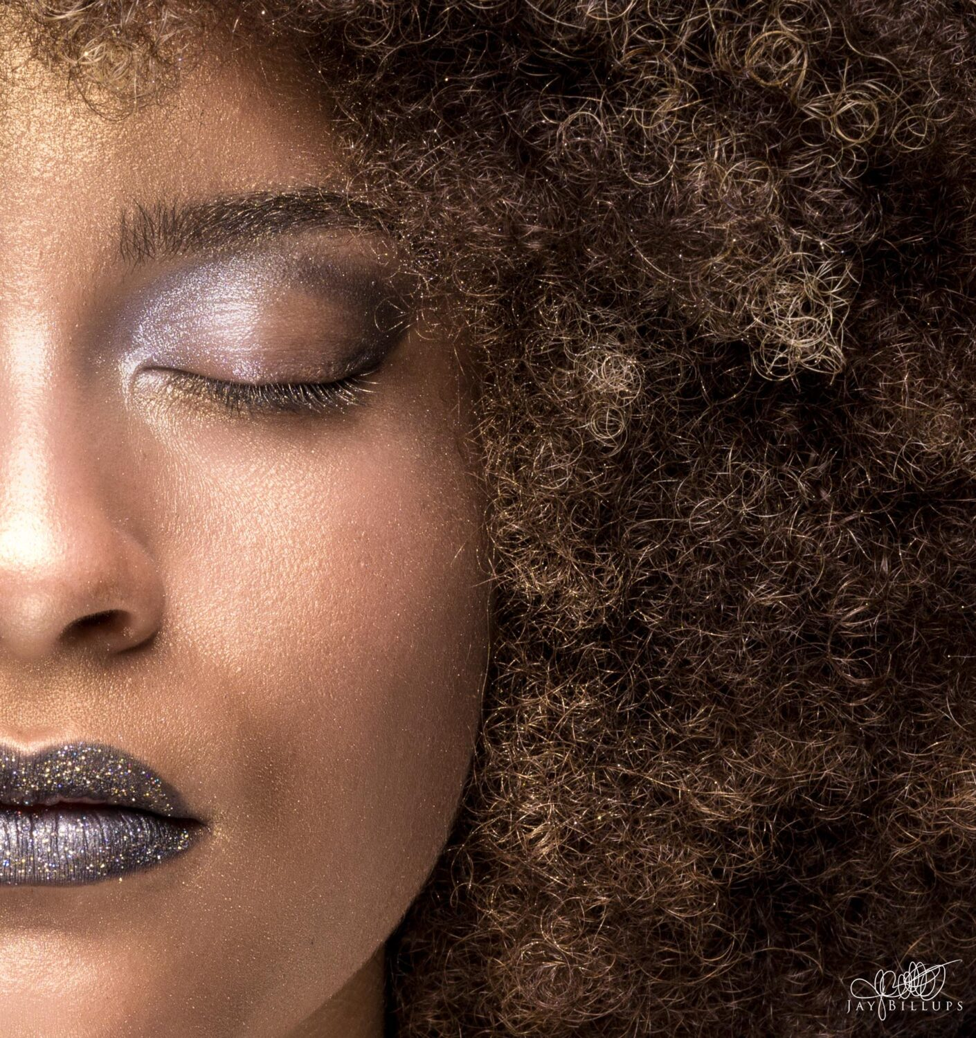 Close up of an`African American woman with her eyes closed. Afro taking up half of the frame