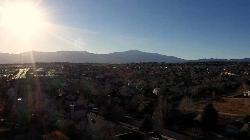 Aerial video near sunset of Colorado Springs neighborhood with Pikes Peak off in the distance, Sun glaring and flaring in lens