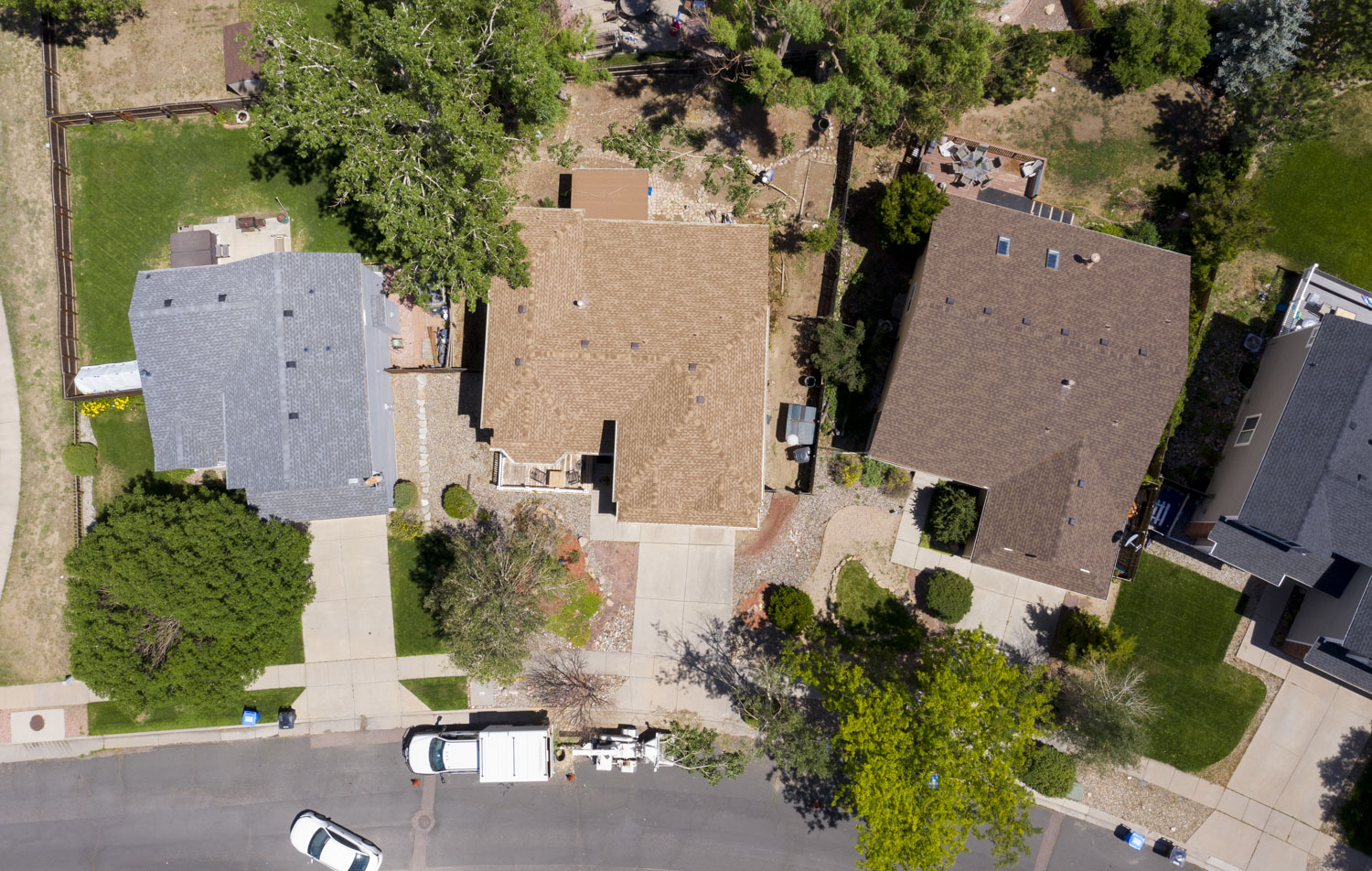 Aerial view of three residential homes. Good shot to survey roofs for damage. Tree service in action clearing branch and pruning for safety