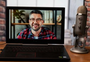 Host of virtual meeting on a laptop computer with mic prop - virtual portrait for marketing