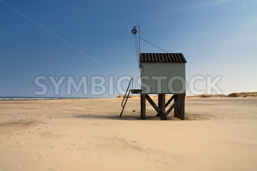 Cabin with a view on sand dunes, beach and sea - Jan Brons Stock Images