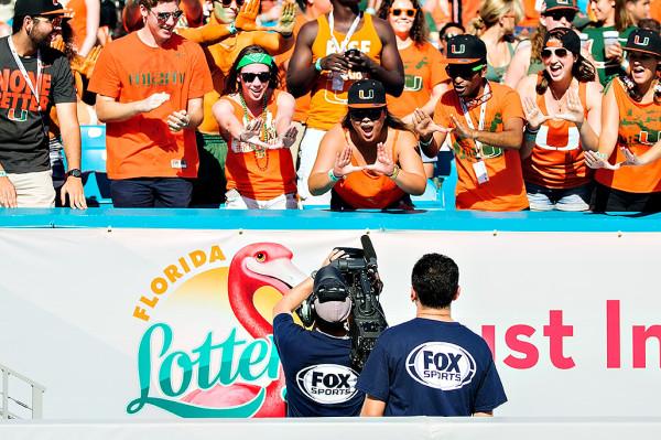 Miami Hurricane fans ham it up for the tv crew