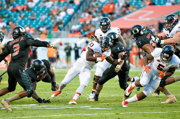 Virginia RB Olamide Zaccheaus tries to evade the Hurricanes defense